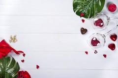 Dois vidros de vinho com corações vermelhos, as pétalas cor-de-rosa e os doces do chocolate fotos de stock royalty free