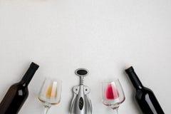 Dois vidros de vinho com vinho vermelho e branco, garrafas do vinho tinto e vinho branco, corkscrew no fundo branco horizontal Imagem de Stock Royalty Free