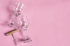 Dois vidros de vinho e um corkscrew em um fundo cor-de-rosa Foto de Stock Royalty Free