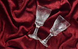Dois vidros de vinho retros vazios em um fundo de seda vermelho Foto de Stock