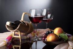 Dois vidros de vinho tinto, a garrafa no suporte da palha e na placa de madeira com videiras e as maçãs situadas no espelho preto Foto de Stock