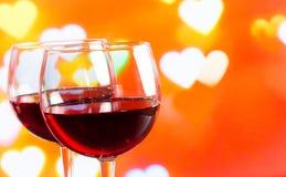 Dois vidros de vinho tinto no bokeh da decoração dos corações iluminam o fundo Fotografia de Stock