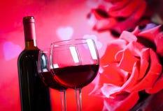Dois vidros de vinho tinto no fundo das rosas vermelhas do borrão Foto de Stock