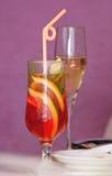 Dois vidros de vinho transparentes de vidro com um cocktail e um champanhe em um fundo cor-de-rosa fotografia de stock royalty free