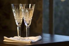 Dois vidros de Waterford Champagne na tabela de madeira Fotografia de Stock