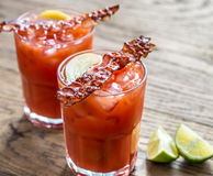 Dois vidros do Bloody Mary com fatias de toucinho do bacon fotografia de stock