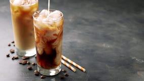 Dois vidros do café frio em um fundo preto O café com gelo derrama o creme ou o leite Movimento lento filme