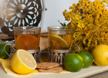 Dois vidros do chá preto nos suportes de vidro, nos alguns biscoitos, em limões maduros e em cais em um linho surgem contra o fun Fotografia de Stock