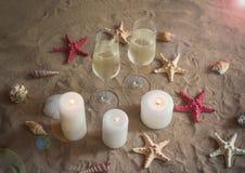 Dois vidros do champanhe, das velas, dos escudos e das estrelas do mar na praia da areia imagens de stock