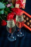 Dois vidros do champanhe, de rosas vermelhas e de doces em um fundo preto imagem de stock royalty free