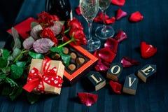Dois vidros do champanhe, de rosas vermelhas, de pétalas, de caixa de presente com fita vermelha, de chocolates e de palavras de  imagem de stock royalty free