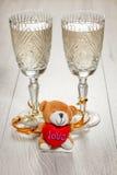 Dois vidros do champanhe e do brinquedo do dia de Valentim carregam Fotos de Stock