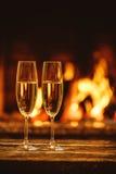 Dois vidros do champanhe efervescente na frente da chaminé morna C Fotografia de Stock Royalty Free