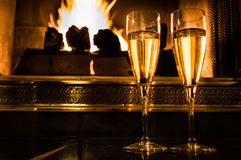Dois vidros do champanhe na frente de um fogo romântico Foto de Stock