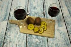 Dois vidros do fruto em uma parte superior de madeira, vintage do vinho tinto e de quivi Imagens de Stock Royalty Free