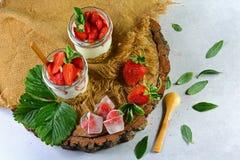 Dois vidros do iogurte fresco saudável da morango com bagas, as cookies de farinha de aveia colher de madeira e a hortelã frescas fotos de stock