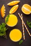 Dois vidros do suco de laranja e da hortelã recentemente espremidos em um fundo do marrom escuro Vista superior Imagem de Stock