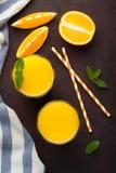 Dois vidros do suco de laranja e da hortelã recentemente espremidos em um fundo do marrom escuro Vista superior Foto de Stock Royalty Free