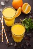 Dois vidros do suco de laranja e da hortelã recentemente espremidos em um fundo do marrom escuro Vista superior Fotos de Stock Royalty Free