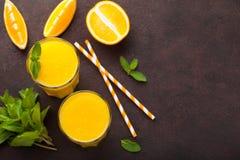 Dois vidros do suco de laranja e da hortelã recentemente espremidos em um fundo do marrom escuro Vista superior com espaço da cóp Imagens de Stock Royalty Free