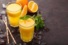 Dois vidros do suco de laranja e da hortelã recentemente espremidos em um fundo do marrom escuro Vista superior com espaço da cóp Fotografia de Stock