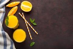 Dois vidros do suco de laranja e da hortelã recentemente espremidos em um fundo do marrom escuro Vista superior com espaço da cóp Fotos de Stock