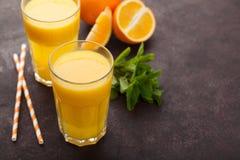 Dois vidros do suco de laranja e da hortelã recentemente espremidos em um fundo do marrom escuro Vista superior com espaço da cóp Fotos de Stock Royalty Free