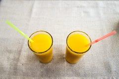 Dois vidros do suco de laranja no fundo do pano de saco dri saudável Fotos de Stock Royalty Free