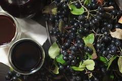 Dois vidros do suco fresco do melanocarpa preto de Aronia das bagas do chokeberry perto dos ramos com bagas pretas Vista superior imagens de stock