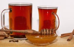 Dois vidros do T preto e de um prato pequeno com mel em um fundo branco Fotografia de Stock Royalty Free