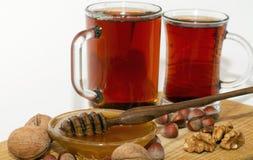 Dois vidros do T preto e de uma bacia com mel e dipper do mel na tabela de madeira Foto de Stock Royalty Free