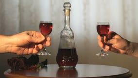 Dois vidros do tim-tim das mãos com um licor da cor vermelha filme