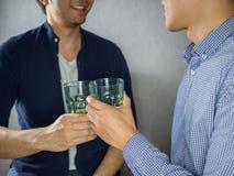 Dois vidros do tinido dos homens e partying perto acima Fotos de Stock Royalty Free