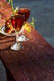 Dois vidros do vinho cor-de-rosa caseiro e das uvas Fotografia de Stock