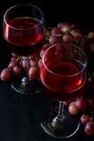 Dois vidros do vinho cor-de-rosa caseiro e das uvas Imagem de Stock