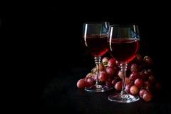 Dois vidros do vinho cor-de-rosa caseiro e das uvas Fotos de Stock Royalty Free