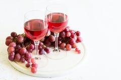 Dois vidros do vinho cor-de-rosa caseiro e das uvas Foto de Stock Royalty Free