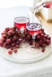 Dois vidros do vinho cor-de-rosa caseiro e das uvas Fotos de Stock