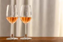 Dois vidros do vinho de Rosa na tabela de madeira a comemorar para um par imagens de stock