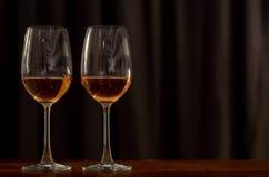 Dois vidros do vinho de Rosa na tabela de madeira a comemorar para um par foto de stock