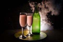 dois vidros do vinho e da garrafa sobre o fundo nevoento tonificado Imagem de dois vidros de vinho com champanhe os esboços e as  Imagens de Stock