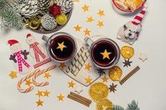 Dois vidros do vinho ferventado com especiarias na tabela do Natal nas festões do fundo e nos ramos do abeto O cão - símbolo do fotografia de stock