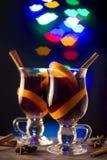 Dois vidros do vinho ferventado com especiarias no fundo dos bordos do bokeh Imagens de Stock Royalty Free