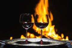 Dois vidros do vinho no fundo do fogo Fotografia de Stock Royalty Free