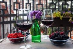 Dois vidros do vinho seco vermelho com bagas e violetas no balcão sérvio com opinião da cidade Foto de Stock