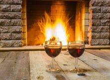 Dois vidros do vinho tinto antes da chaminé Fotos de Stock Royalty Free