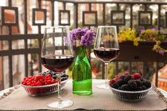 Dois vidros do vinho tinto com bagas e violetas no balcão sérvio com opinião da cidade Imagens de Stock