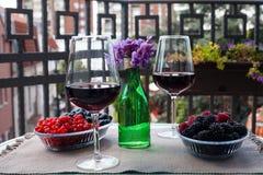 Dois vidros do vinho tinto com bagas e violetas no terraço sérvio com opinião da cidade Imagens de Stock