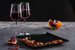Dois vidros do vinho tinto com fruto e porcas da romã Fundo escuro imagem de stock