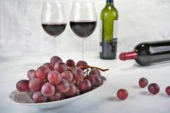 Dois vidros do vinho tinto com garrafa e uvas Fotografia de Stock Royalty Free